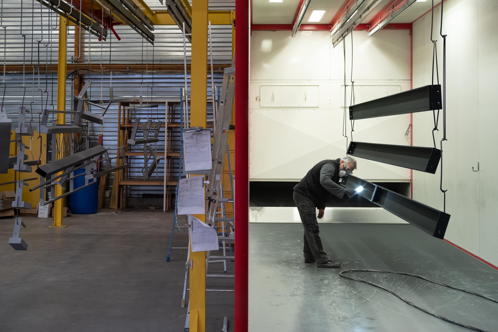 Penché sur une structure à l'aspect métallique, dans un atelier, une personne portant des lunettes et un masque de protection examine la pièce à l'aide d'une lampe