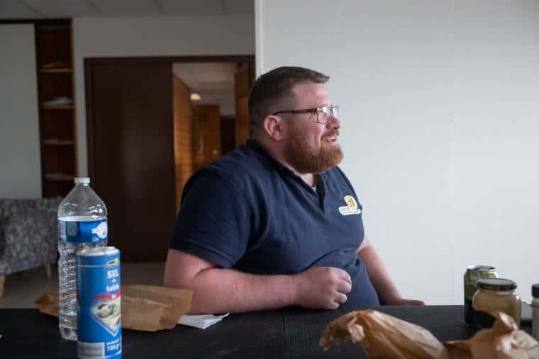 Arnaud Pointereau, accoudé à une table à manger, regarde vers la droite. Sur la table sont diposés une bouteille d'eau, de la moutarde, un sandwich, une canette de jus de fruit et des sacs en papier. À l'arrière on aperçoit un intérieur de maison