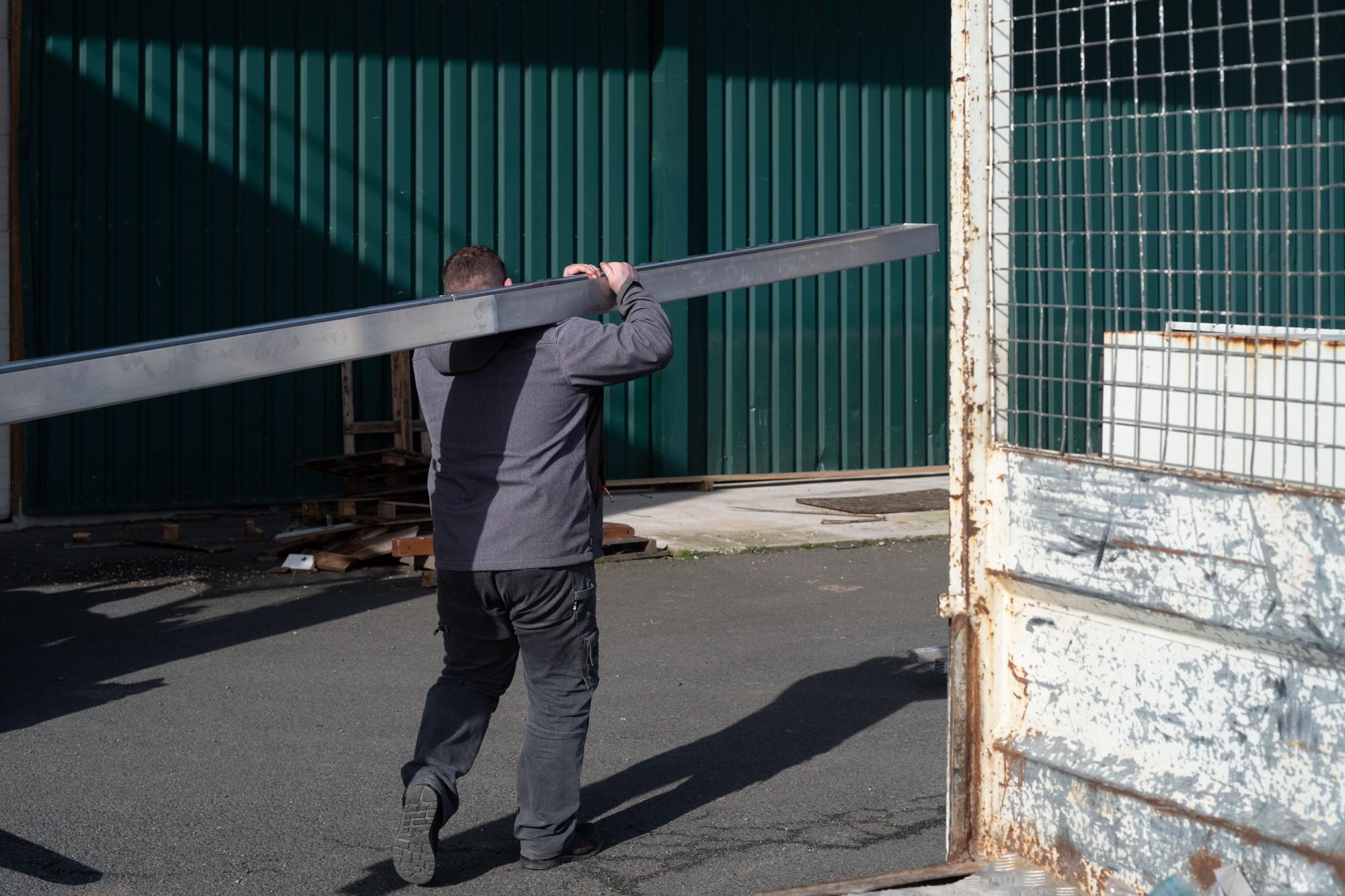 Arnaud, de dos, tansporte une longue structure métallique en extérieur
