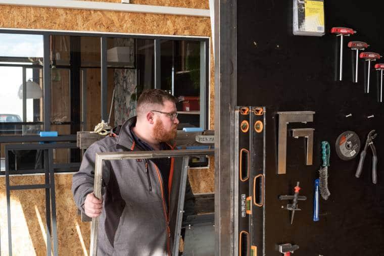 Arnaud transporte un cadre métallique. dans un atelier. Au premier plan, des outils sont accrochés à un pan de mur. À l'arrière plan, une grande fenêtre permet d'apercevoir une autre pièce, ainsi qu'une autre fenêtre sur l'extérieur.