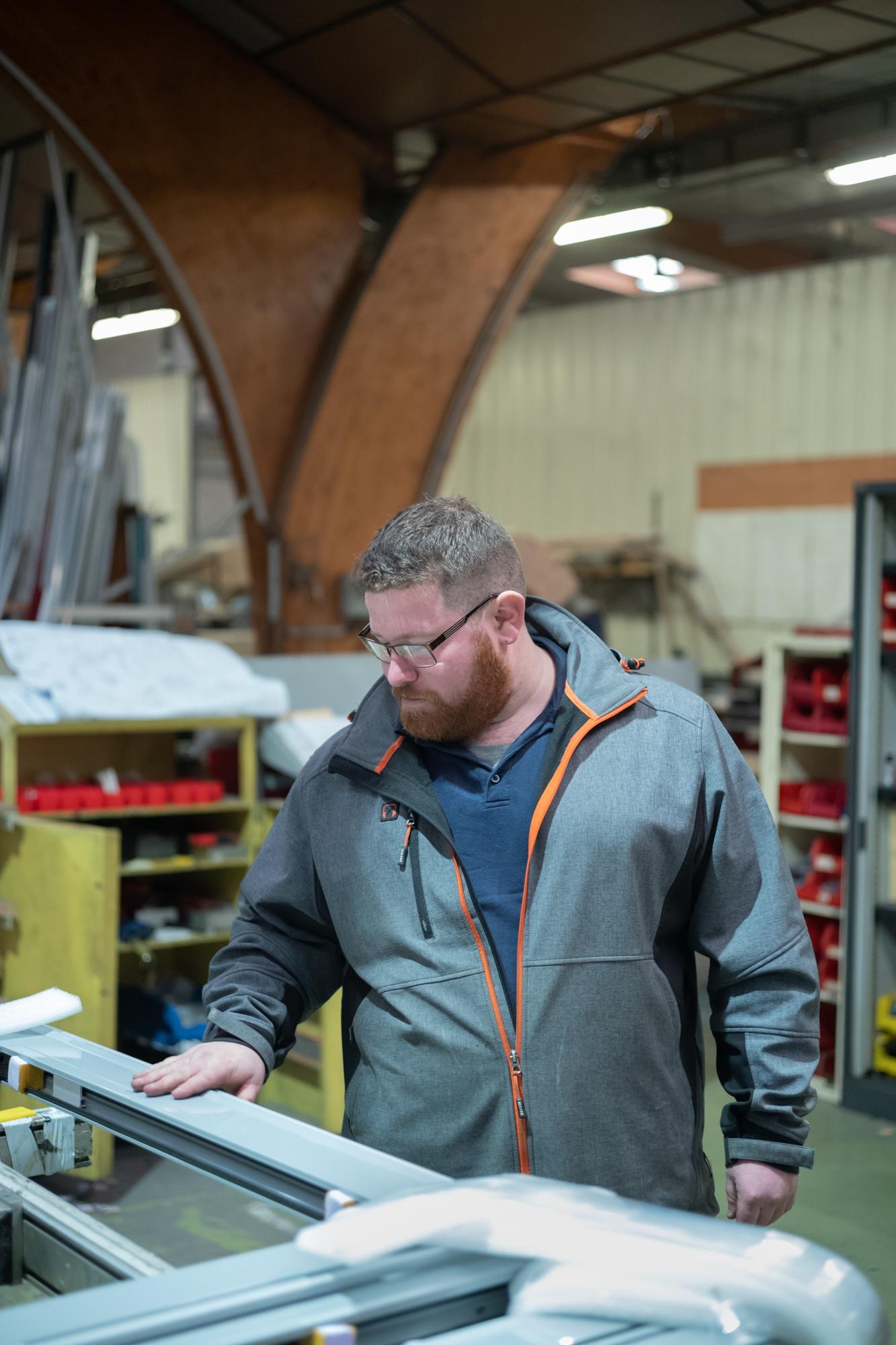 Arnaud passe sa main sur un revêtement laqué dans un atelier