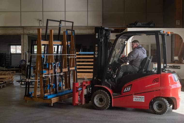 Arnaud manœuvre un transpalette sur lequel sont chargées diverses structures métalliques, au sein d'un atelier