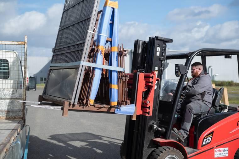Arnaud, aux commandes d'un transpalette, charge des matériaux sur son camion, en extérieur