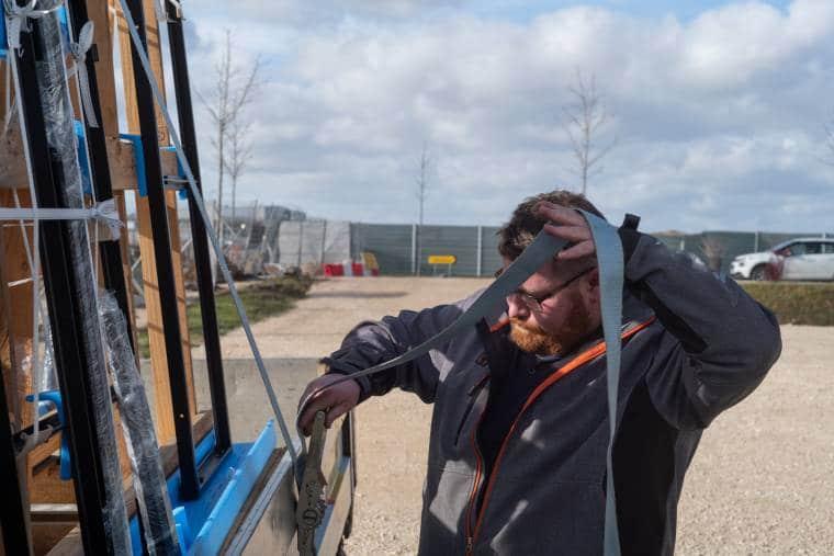 Arnaud sangle les matériaux à son camion