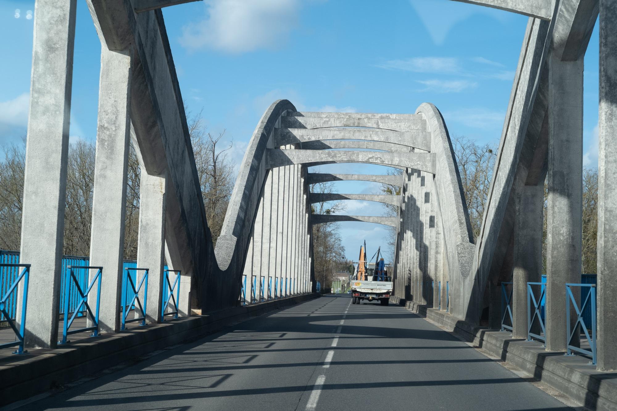 Le camion d'Arnaud est aperçu de dos, traversant un pont surmonté de structures bétonnées