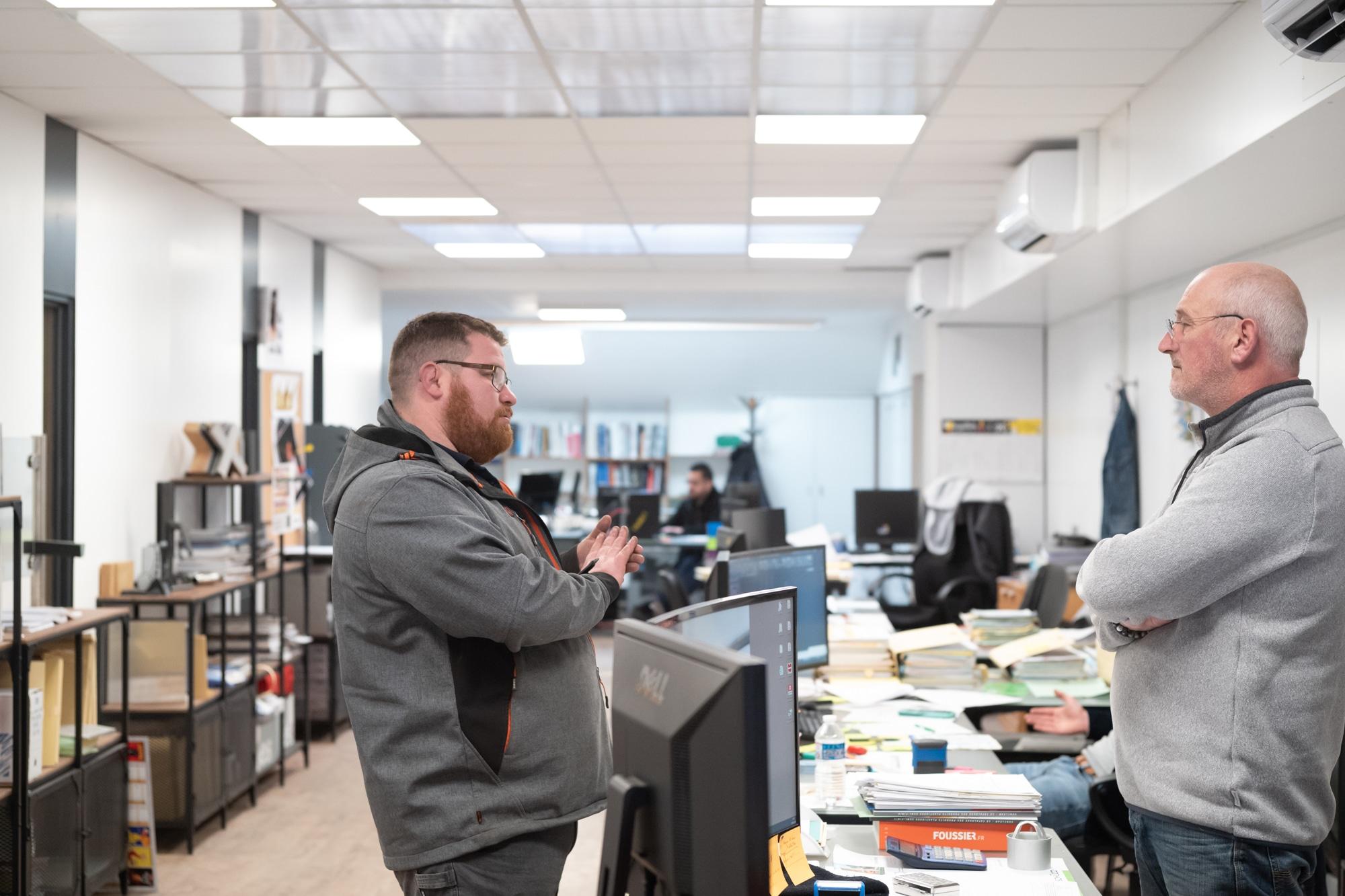 Arnaud, se tenant debout d'un côté d'un bureau, discute avec une personne également levée, derrière son bureau