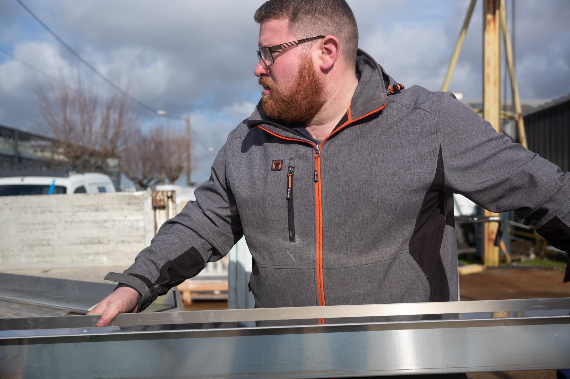 Arnaud, de face, transporte une structure métallique en extérieur