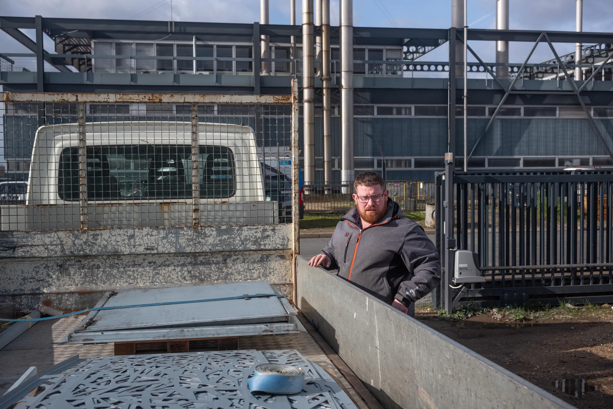 Debout à côté de son camion, situé devant un bâtiment industriel, Arnaud examine le contenu qu'il transporte