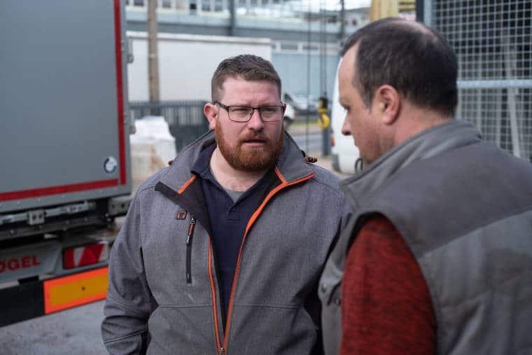 Arnaud, de face, discute avec une personne de dos, en extérieur