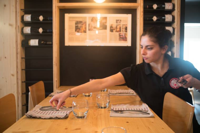 Océane finit de dresser une table du restaurant.