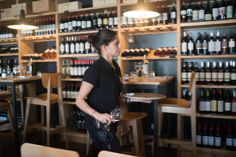 Un plateau dans la main gauche et deux verres en main droite, Océane passe devant un mur orné de bouteilles de vin dans la salle du restaurant.