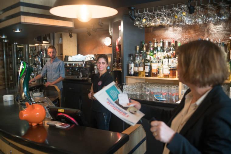 Océane, se tenant derrière le bar près d'un serveur, regarde la responsable du Trinquet en souriant.
