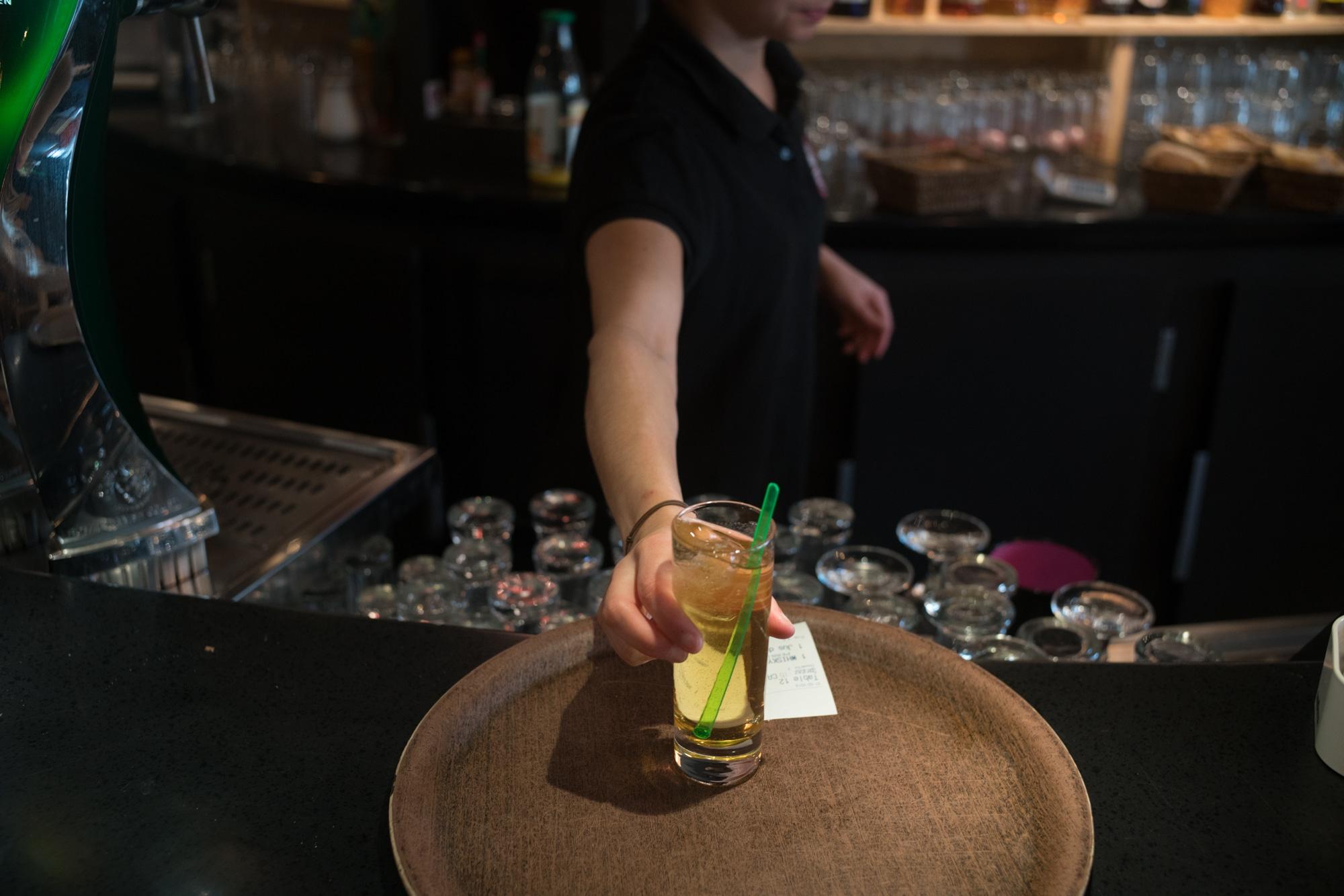 La main d'Océane dépose une boisson sur un plateau à côté de l'addition.