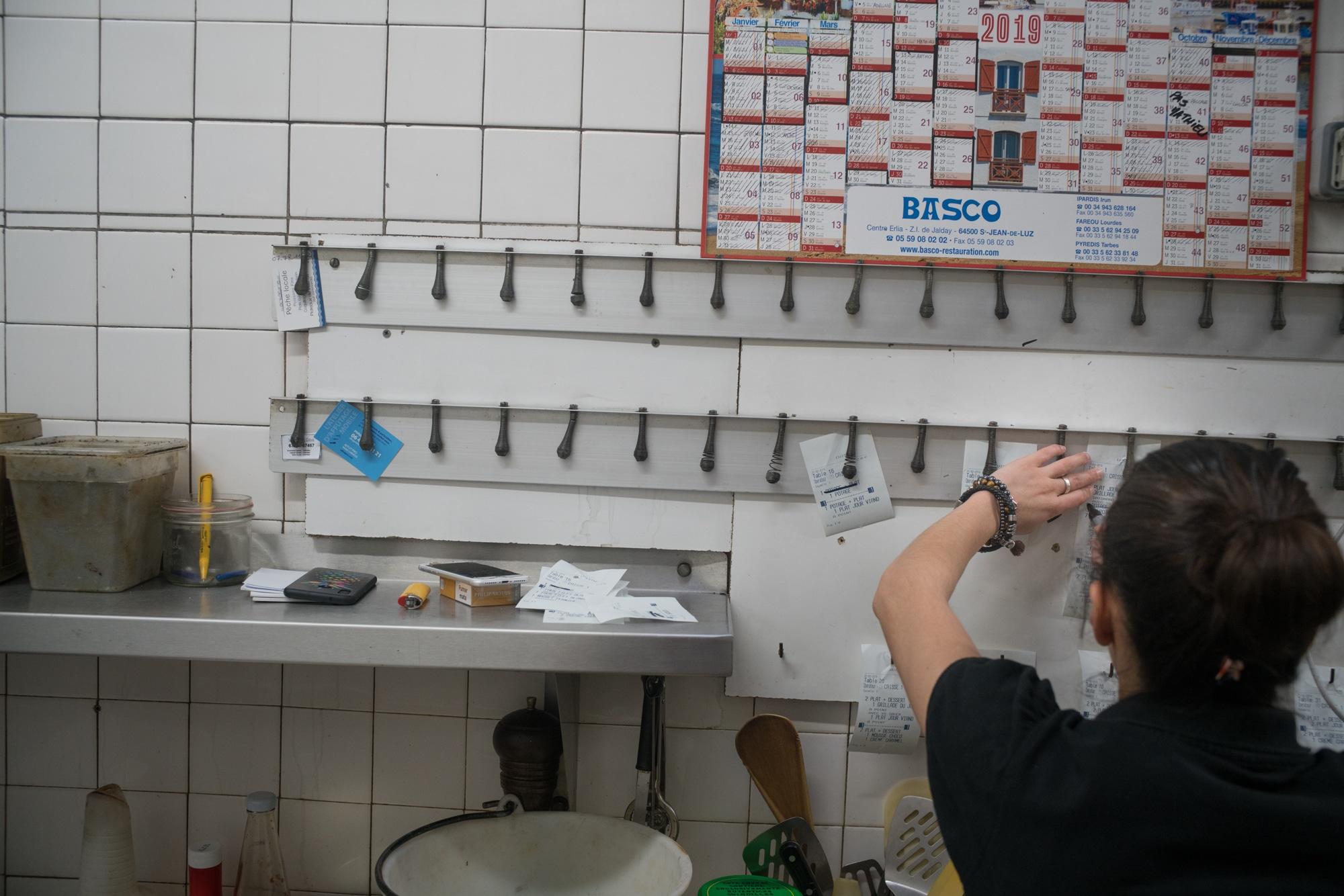 En cuisine, Océane annote des tickets de commande accrochés au mur.