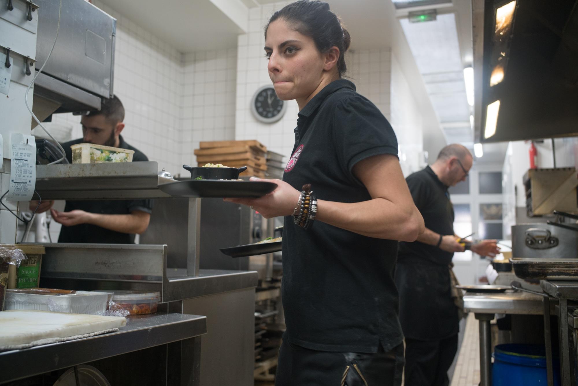Un plat dans chaque main, Océane s'apprête à quitter la cuisine.