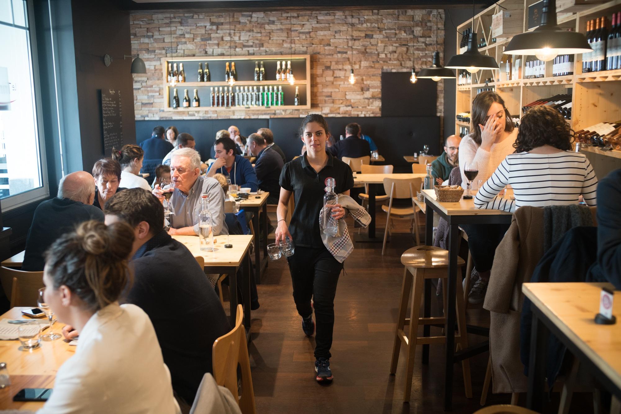 Océane, marchant au milieu de la salle du restaurant, porte une bouteille et des verres.