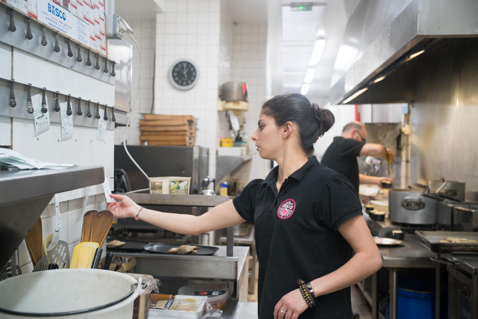 En cuisine, Océane décroche une note du mur des commandes.