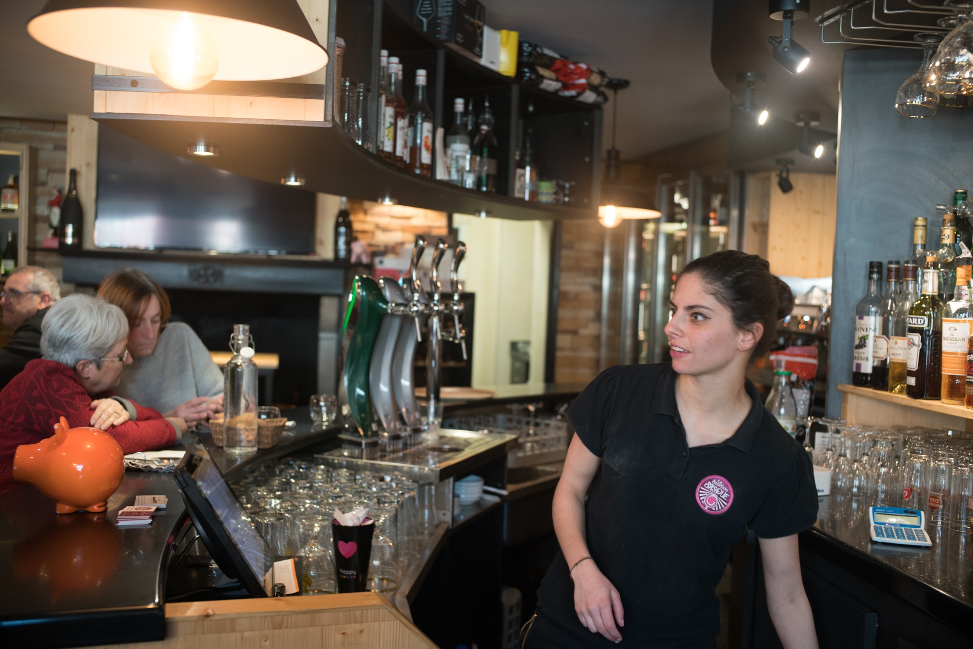Océane, derrière le bar, regarde attentivement la salle.