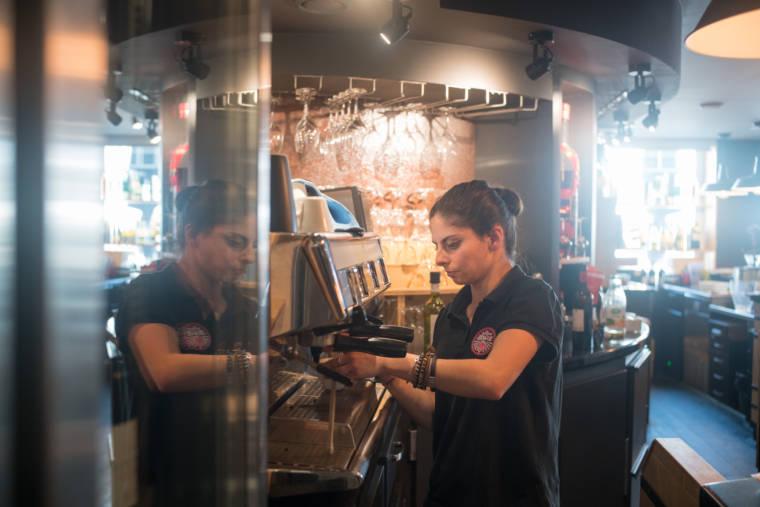 Océane prépare des cafés à la machine du restaurant.