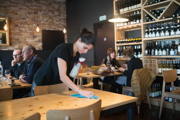Océane tient un vaporisateur dans la main gauche et nettoie une table du restaurant de la main droite.