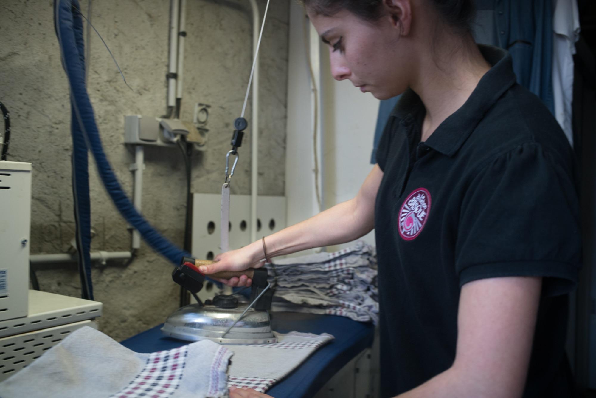 Océane presse des serviettes à l'aide d'un fer à repasser.
