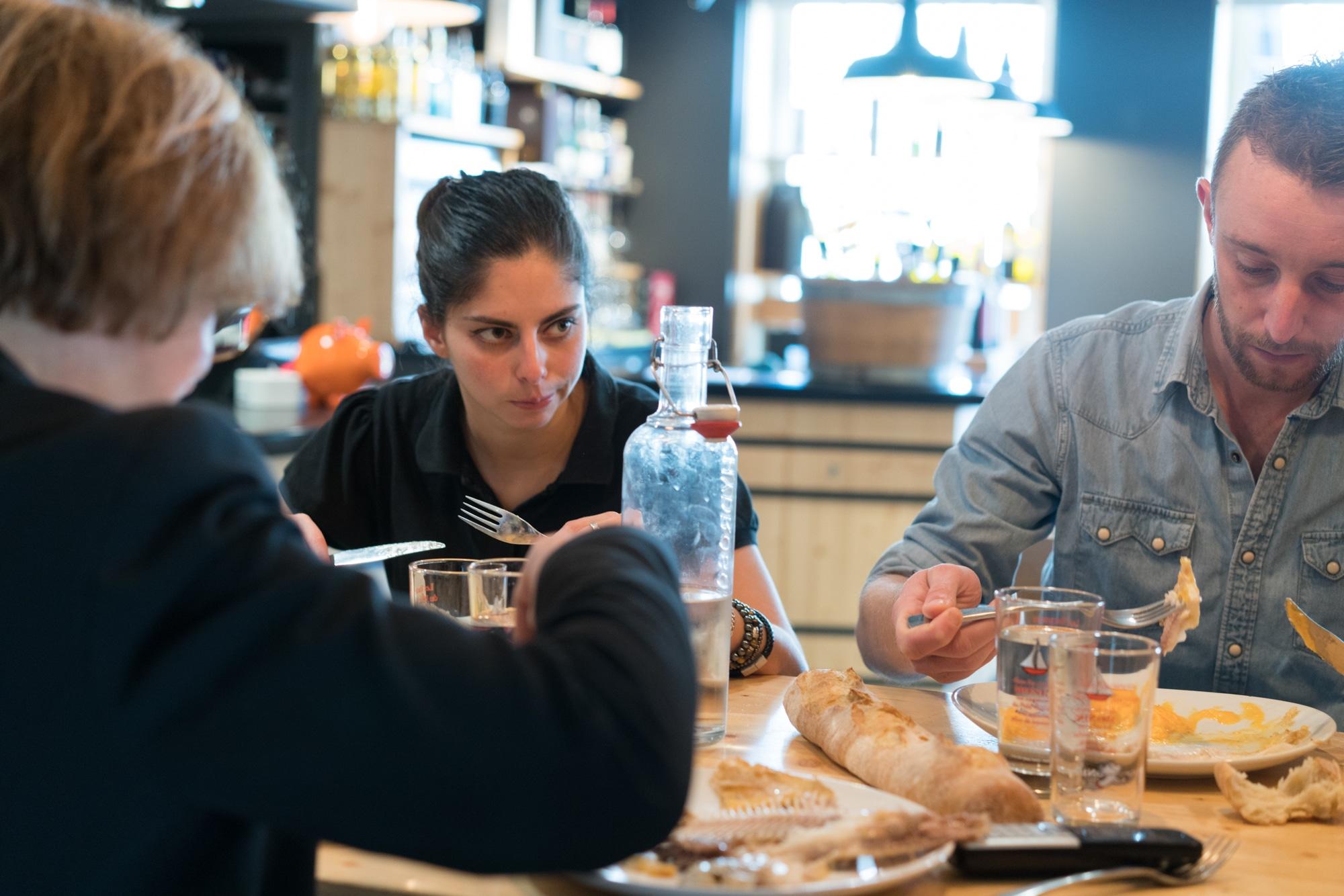 Océane se restaure à table, entourée du personnel du restaurant.
