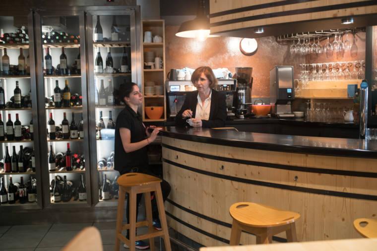Assise au bar du restaurant, Océane discute avec la responsable du Trinquet.