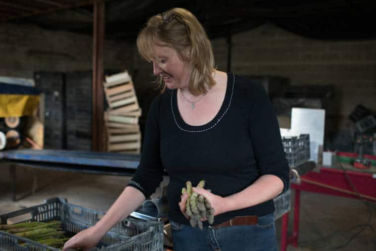 Sophie, souriante, récupère des asperges dans une cagette.