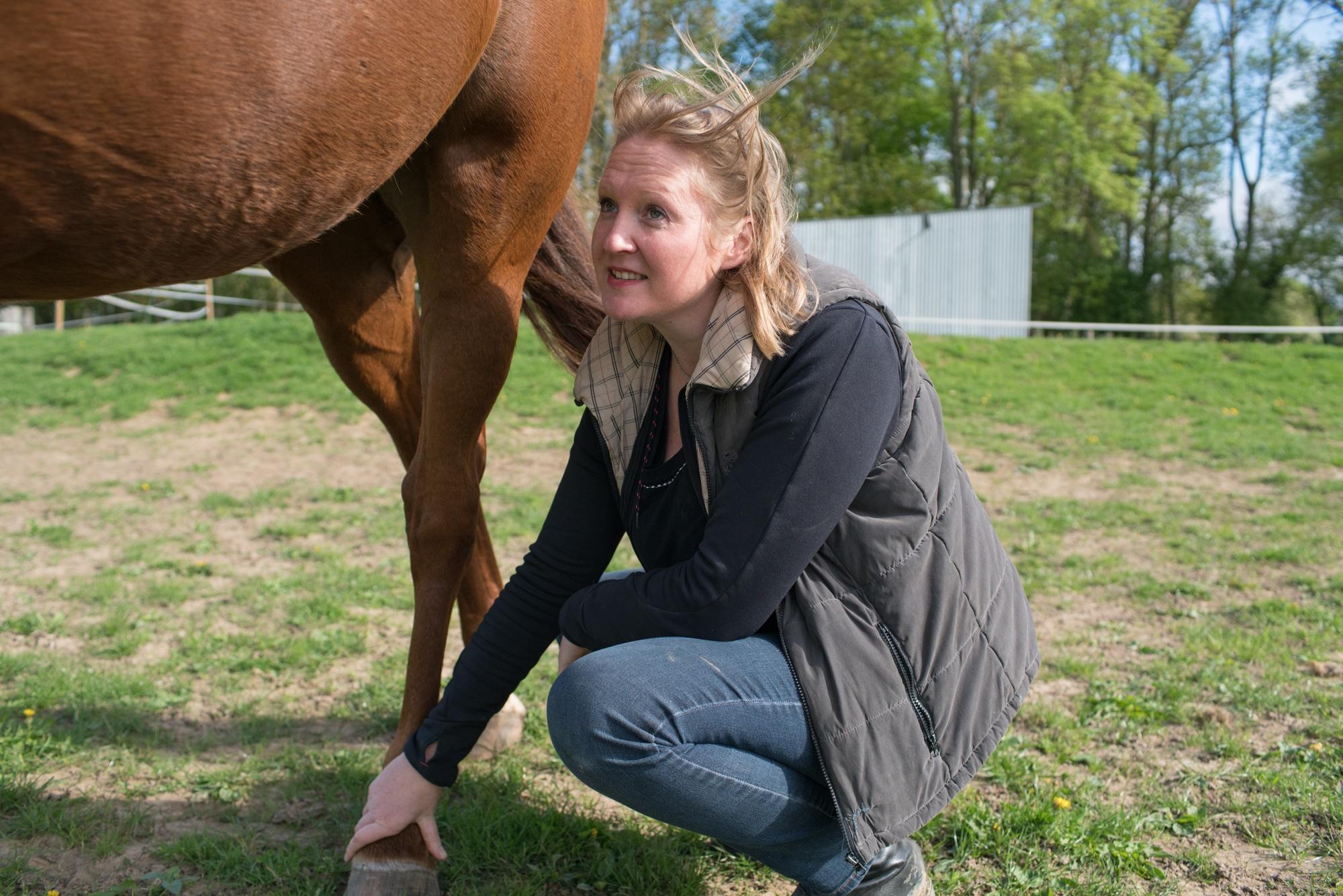Sophie, accroupie, saisit le sabot d'un cheval.