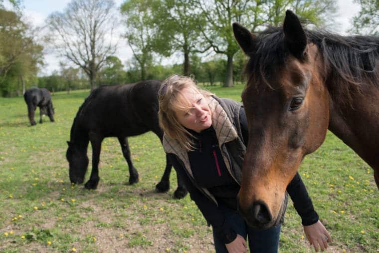Sophie se tient dans un champ avec ses chevaux