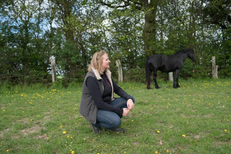 Sophie, accroupie dans le pré. On aperçoit un cheval au second plan.